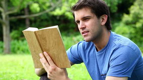 Serious man reading a novel. In a park stock footage