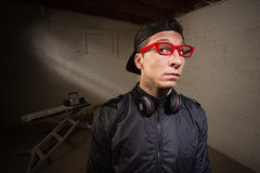 Serious Man in Red Eyeglasses. Conceited young man with red eyeglasses and earphones stock photos