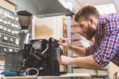 Serious man repairing broken coffee machine Stock Photos