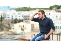Serious man scouting sitting on a ledge on vacation royalty free stock photos
