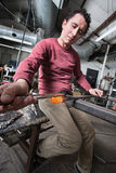 Man Shaping Glass Art. Serious man shaping hot glass object with big tools Royalty Free Stock Photo