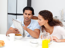 Serious man showing the newspaper to his wife Stock Photos
