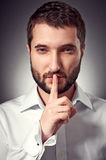 Serious man showing silent sign Stock Photo