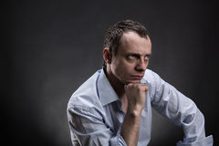 Serious man sits thinking Royalty Free Stock Image