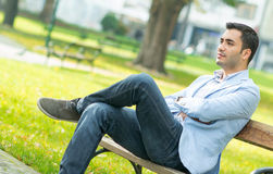 Serious man sitting on bench Stock Images