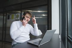 Man is sitting in a modern office near the window at the table, and talks over the phone freelancer works stock photo