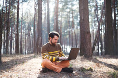 Serious man sitting outdoors using a laptop computer Stock Photos