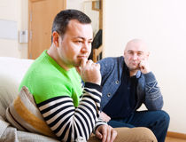 Serious man sitting on sofa. Two adult friends having quarrel at home Stock Photos