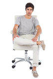 Serious man sitting on a swivel chair Stock Images