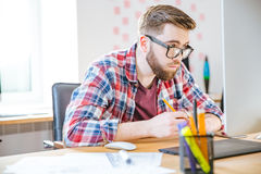 Serious man sitting on workplace and looking over glasses Royalty Free Stock Photo