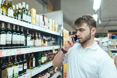 A serious man speaks by telephone at the supermarket. A man chooses alcohol in the store. Royalty Free Stock Photo