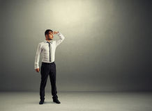 Serious man standing in dark room Royalty Free Stock Photos