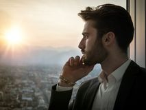 Serious man standing inside modern building. Handsome serious businessman standing inside modern building next to big window, looking out Royalty Free Stock Image