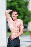Serious Man Standing Outdoors And Flexing Muscles Stock Image
