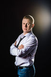 Serious man standing sides in a half-turn with folded hands. Studio shot  flare at background. Royalty Free Stock Photography