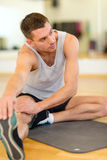 Serious man stretching on mat in the gym Royalty Free Stock Photo