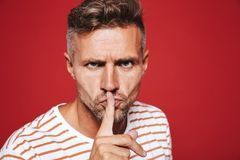 Serious man in striped t-shirt holding index finger on lips with royalty free stock image