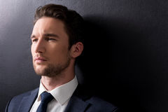 Serious man with stubble is standing against dark background Royalty Free Stock Images