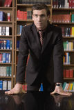 Serious Man In Suit At Library Desk. Serious young man in suit leaning on desk in the library Royalty Free Stock Images
