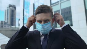 Serious man in suit putting on protective mask, seasonal flu epidemic in country