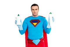 Serious man in superhero costume holding bottles with detergent and looking at camera. Isolated on white royalty free stock image