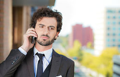 Serious man talking on mobile phone, on a balcony of his apartme. Closeup portrait, classy looking, handsome young, serious, worried business man talking on cell royalty free stock photos