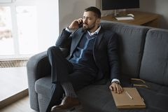 Serious Man in Talking on Smartphone. Cheerful businessman in suit talking on the phone, sitting on sofa in office. Portrait of a bearded concentrated man royalty free stock photo
