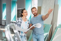 Serious man telling his preferences in renovations. My preferences. Concentrated athletic men pointing at the wall and talking about his preferences in Royalty Free Stock Images