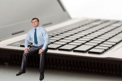 Serious man thinks. A man sitting on laptop thinks Royalty Free Stock Images