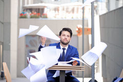 Serious man throwing papers out Stock Image