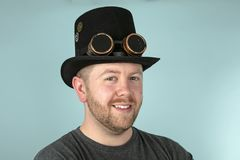 Serious man in a top hat looking solemnly ahead. Serious young bearded man in a top hat looking solemnly at the camera over a grey studio background stock photos