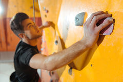 Serious man training in climbing gym. stock image