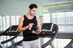 Serious man on treadmill looking at clipboard Royalty Free Stock Images