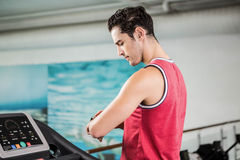 Serious man on treadmill looking at smart watch Stock Photography