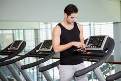 Serious man on treadmill standing with tablet Stock Photos