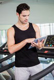 Serious man on treadmill standing with tablet Stock Photography
