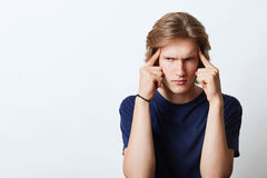 Serious man trying to concentrate, keeping fingers on head, making important decison looking with angry expression. Young business. Man being busy with work Royalty Free Stock Photo