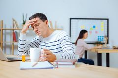 Serious man trying to concentrate on task. Cannot imagine. Ill office worker holding cup in left hand and closing eyes while putting hand on the forehead Royalty Free Stock Photography