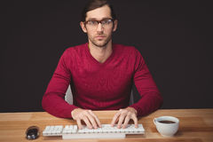 Serious man typing on keyboard with coffee on desk Royalty Free Stock Photography