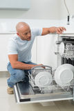 Serious man using dish washer in kitchen Stock Photography