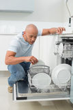 Serious man using dish washer in kitchen Stock Images