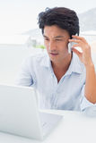 Serious man using his laptop and talking on phone. Outside on a balcony Royalty Free Stock Images