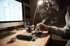 Serious man using scheme soldering iron for repairing motheboard Stock Photography
