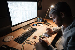 Serious man using soldering iron for fixing smartphone Royalty Free Stock Photo