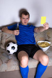 Serious man watching football on tv at home and showing yellow c Royalty Free Stock Photo