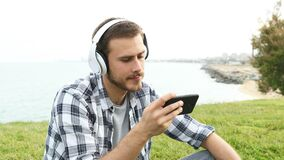 Serious man watching media on phone outdoors stock video