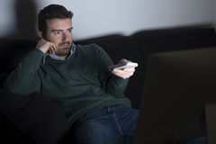 Serious man watching television Royalty Free Stock Photography