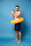 Serious man with water gun standing isolated. Confident young man in sunglasses holding water gun and swimming circle and standing isolated over blue royalty free stock images