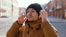 Serious man wear headphones outdoor, included original audio. Listening to music stock video