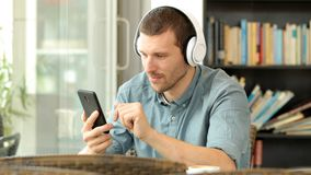 Serious man listening to music on phone in a bar. Serious man wearing headphones listening to music on mobile phone sitting in a bar stock video footage